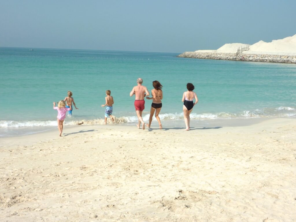 Family running into the sea on a deserted beach