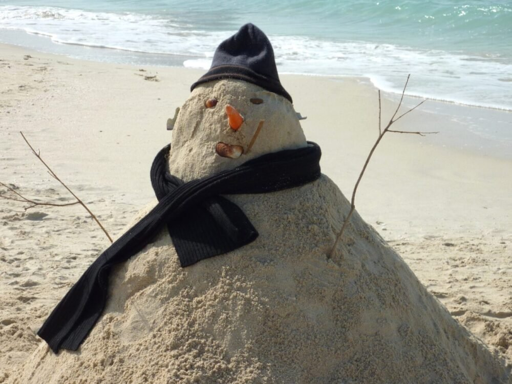 Snowman made out of sand on a beach