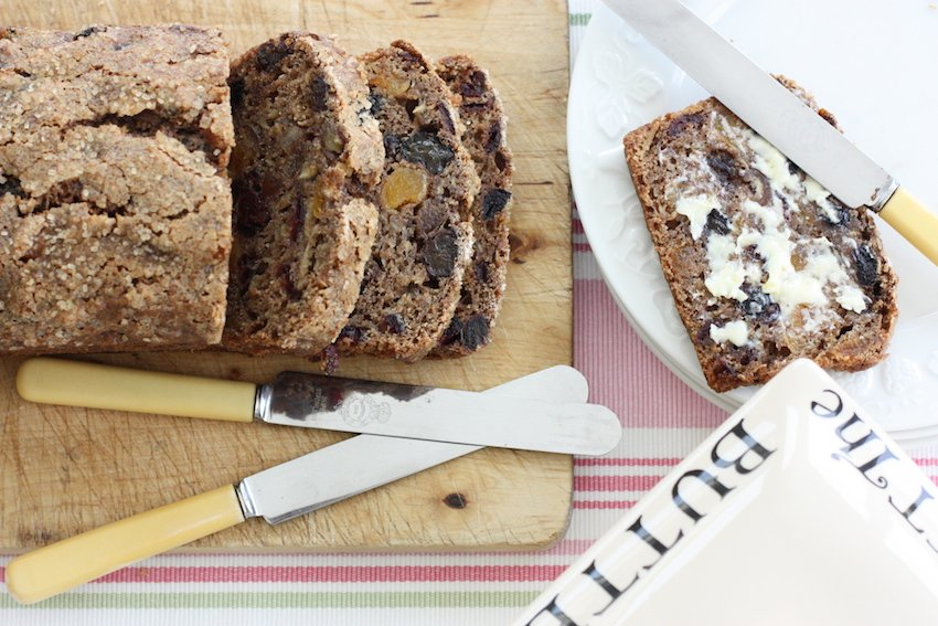 Earl Grey Fruit Loaf sliced on a wooden board with 2 knives and a butter dish