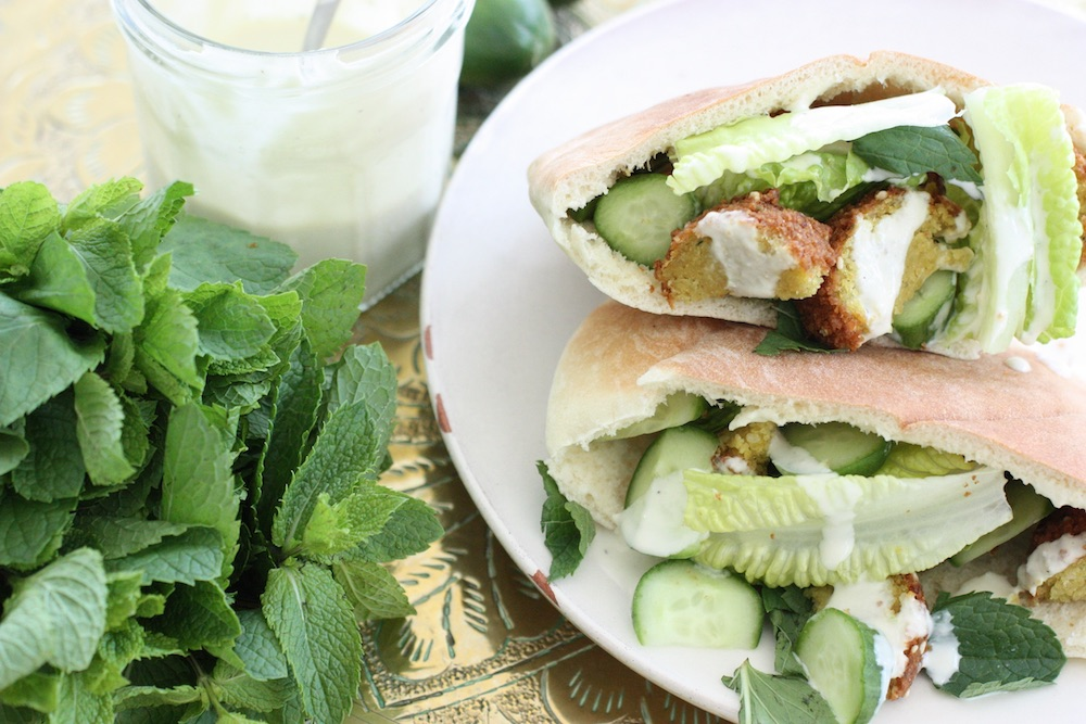 Falafel Stuffed Pita Bread on a white plate with a bunch of mint