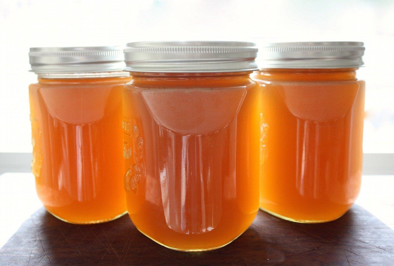 chicken stock in three glass jars