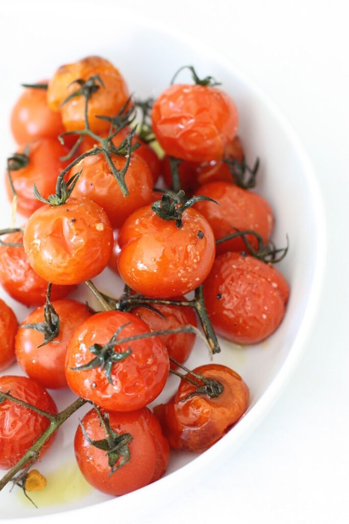 Roasted cherry tomatoes in a flat white bowl