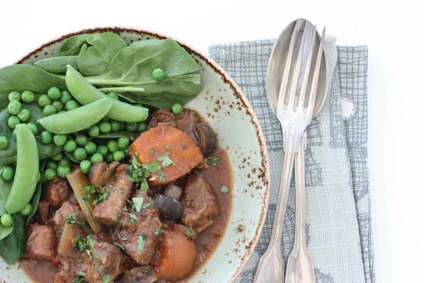 A bowl of slow cooker beef and sausage casserole with cutlery and a napkin