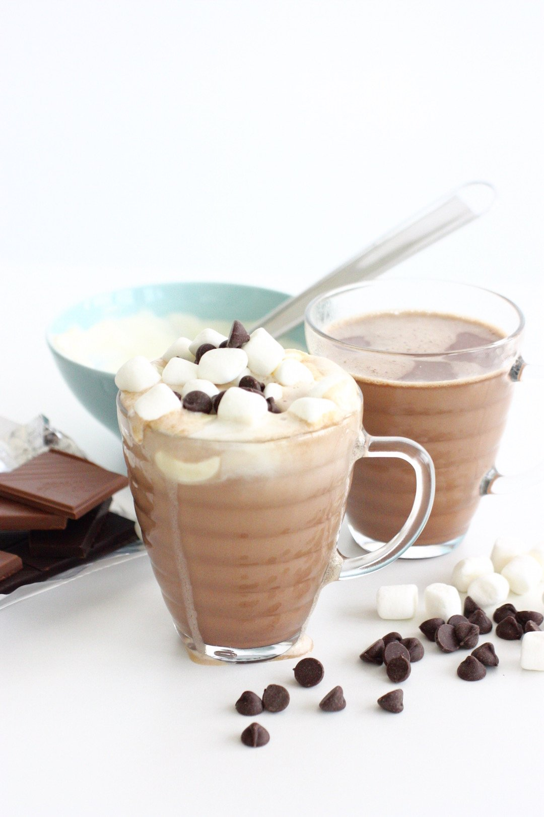 ultimate hot chocolate in glass mugs topped with cream, marshmallows and chocolate chips