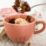 Chocolate mug cake in a pink mug with a spoonful of gooey cake and vanilla ice cream