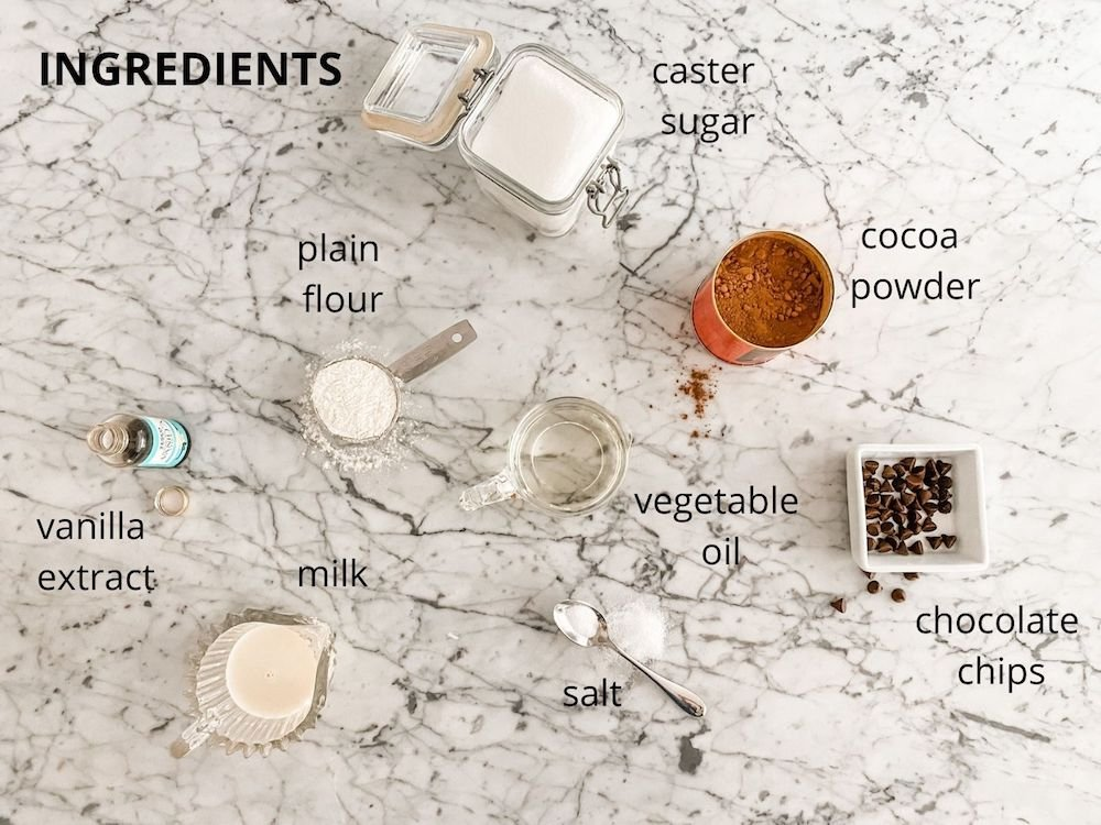 Ingredients for chocolate mug cake laid out on marble worktop