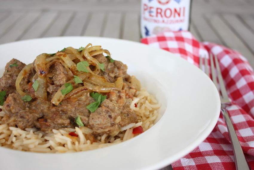 Lamb, Tomato and Coconut Curry in a white dish with a red gingham napkin