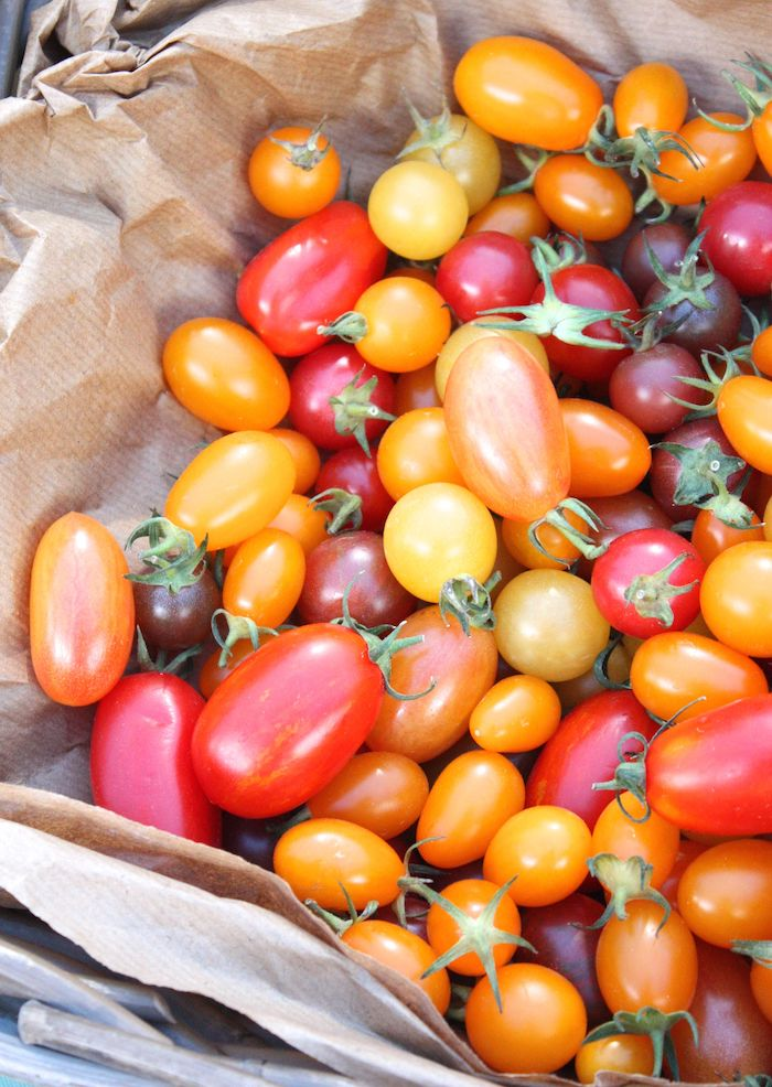 Multi-coloured cherry tomatoes on brown paper