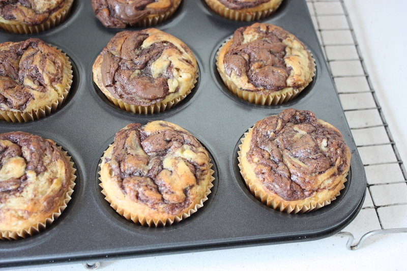 nutella and banana muffins in a muffin tray cooling on a rack