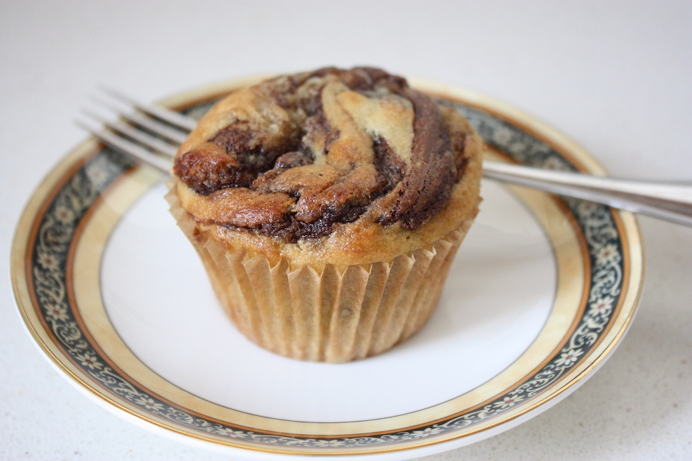 A single Nutella and Banana Muffin on a plate with a fork