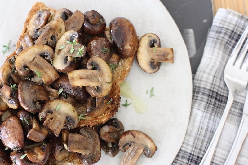 Mushrooms on toast on a white plate shot from above