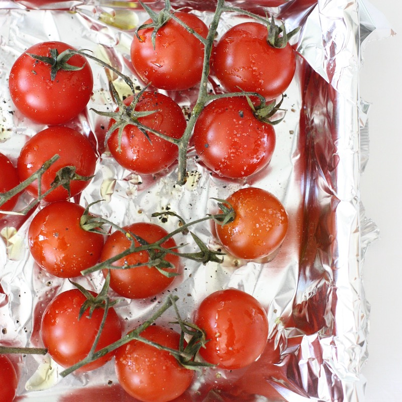 Cherry tomatoes on the vine on a tin foil covered tray and drizzled with olive oil and seasoning