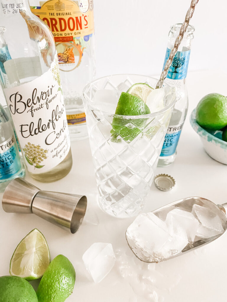 A Simple Gin & Elderflower Cocktail in a tall glass surrounded by the ingredients