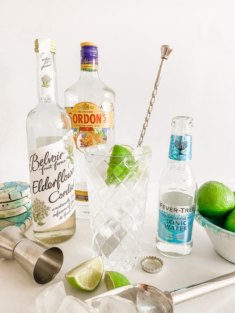 A Gin & Elderflower Cocktail in a tall glass surrounded by ingredients