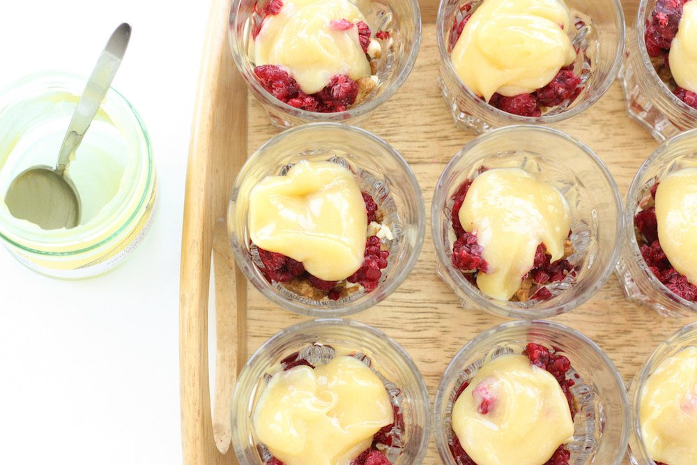 Lemon curd, raspberries and a biscuit base in individual glasses on a wooden tray