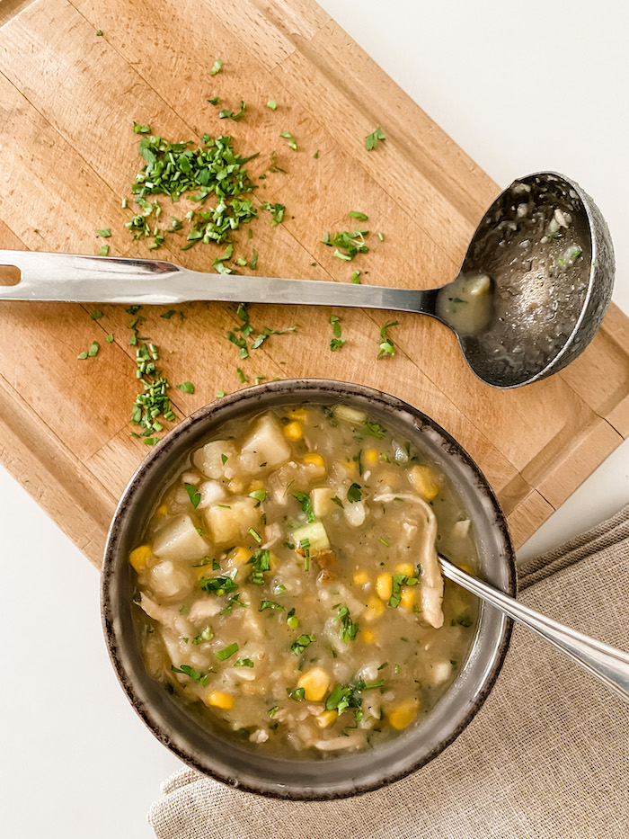 A bowl of chicken and sweetcorn chowder with a ladle on a wooden board