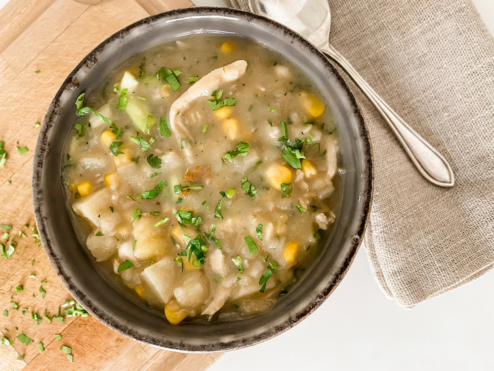 A bowl of chicken and sweetcorn chowder with a spoon on a wooden board