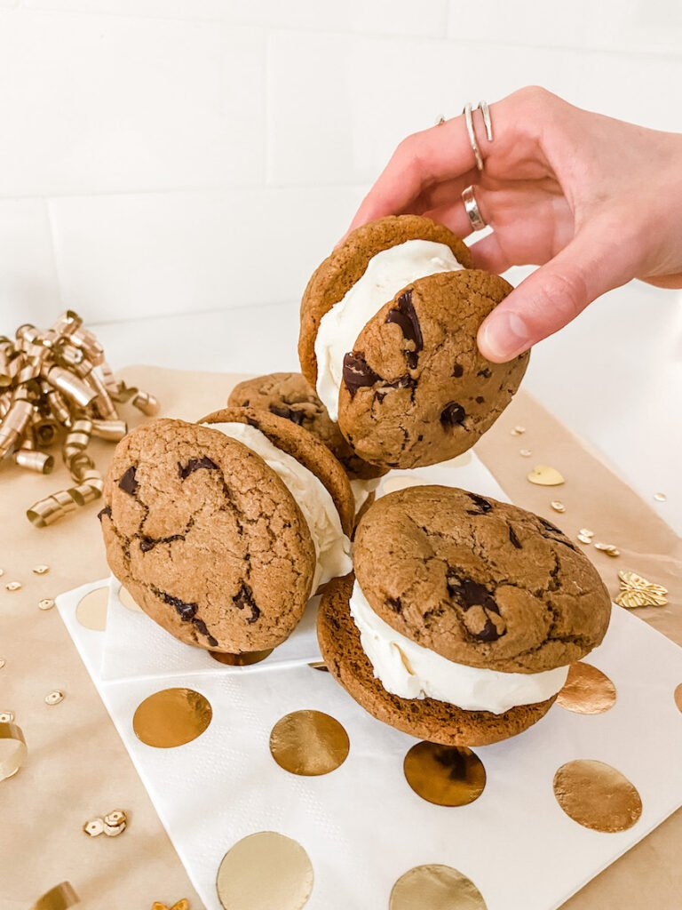 A hand taking one of the Chocolate Espresso Ice Cream Sandwiches off a spotty napkin and surrounded by sparkles and ribbon