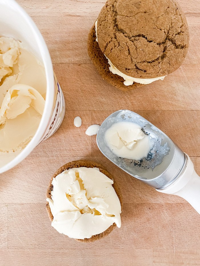 Ice cream being scooped onto a cookie to make an ice cream sandwich