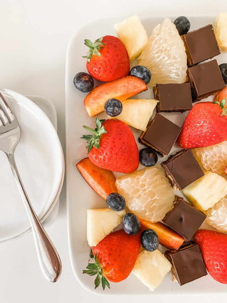 Chocolate tiffin on a white plate with fruits