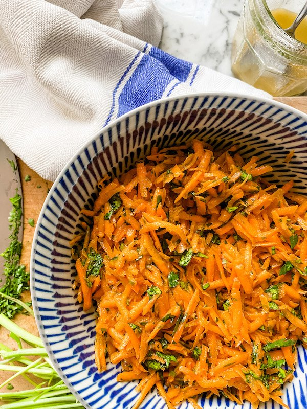 Grated carrot salad in a blue bowl with chopped herbs, a knife and a white tea towel