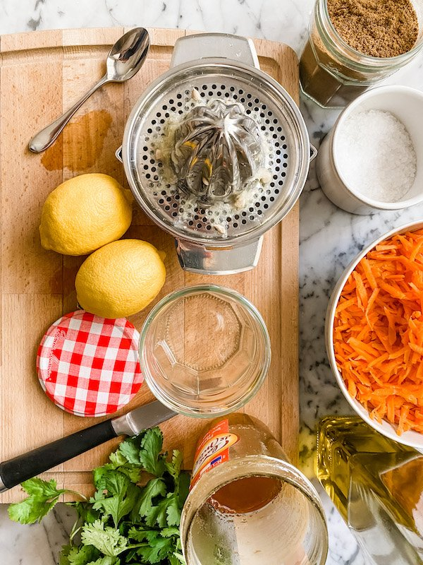 2 lemons, a lemon squeezer, grated carrot and other ingredients on a wooden chopping board