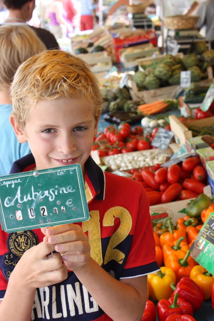 Fruit and vegetables in a market with a boy holding a sign
