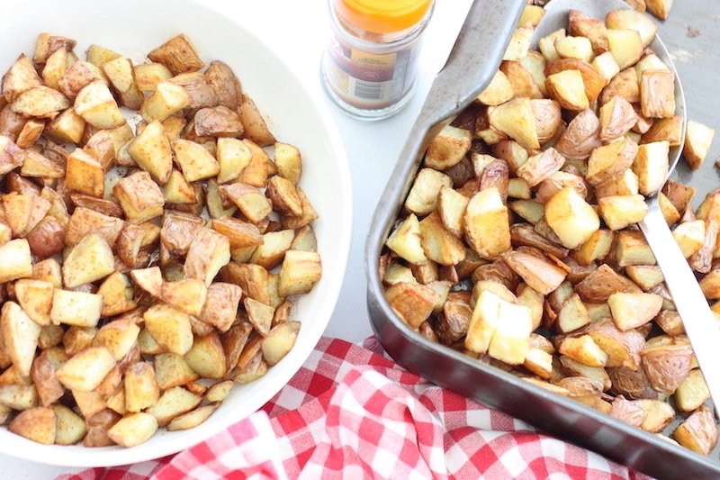 A white bowl of Paprika Potatoes by the side of a baking tray and a red and white gingham napkin