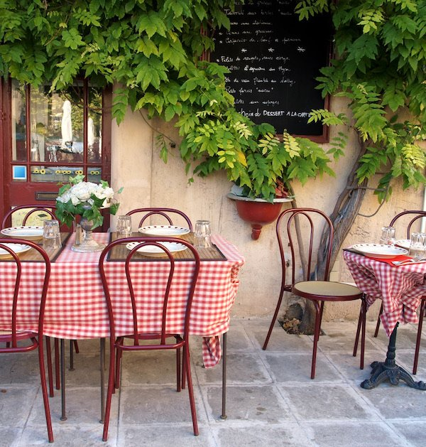 A french pavement cafe with red and white checked tablecloths
