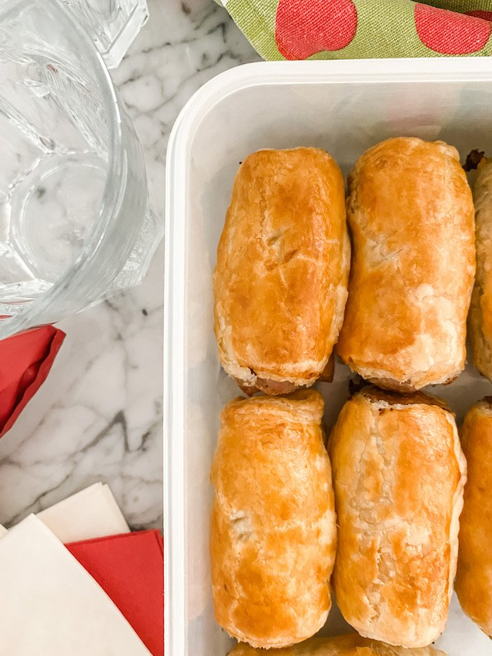 Easy Homemade sausage rolls in a plastic box with paper napkins and a tea towel
