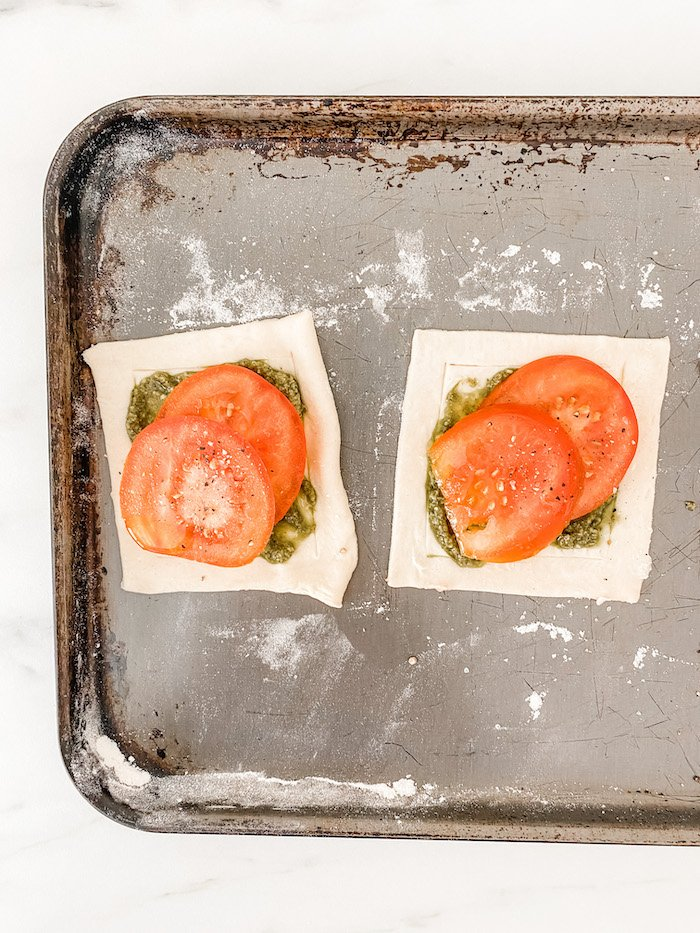 Two small pesto tarts with tomatoes on a baking tray