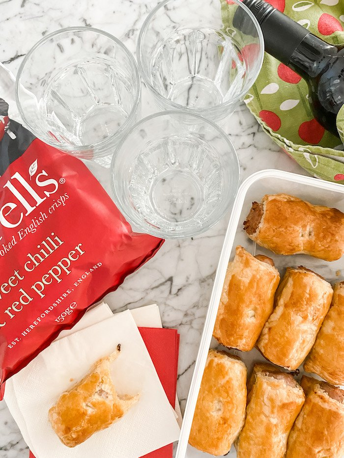 Easy Homemade sausage rolls in a plastic box with a crisps,  a bottle of wine and glasses