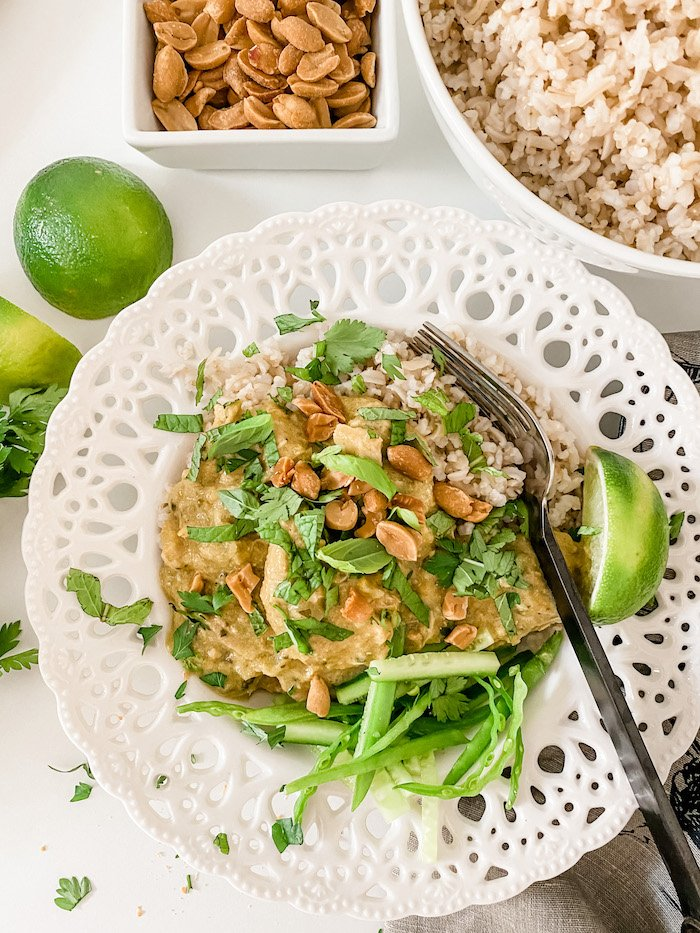 Slow Cooker Lemongrass and Coconut Chicken Curry in a flat white bowl with lots of herbs to garnish and a fork