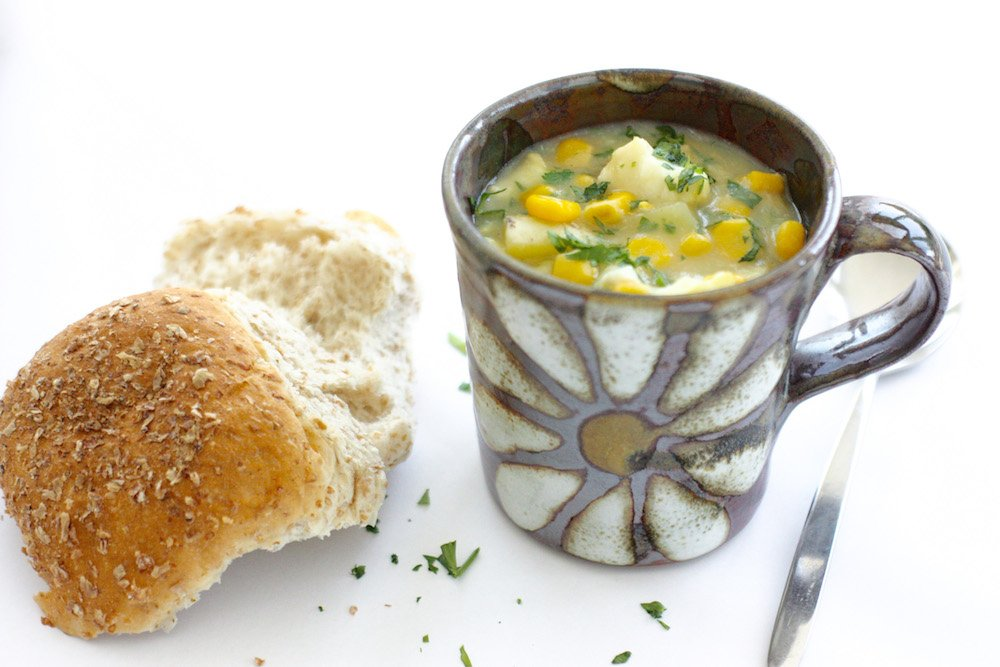 Smoked Haddock and Sweetcorn Chowder in a small brown mug with a bread roll at the side