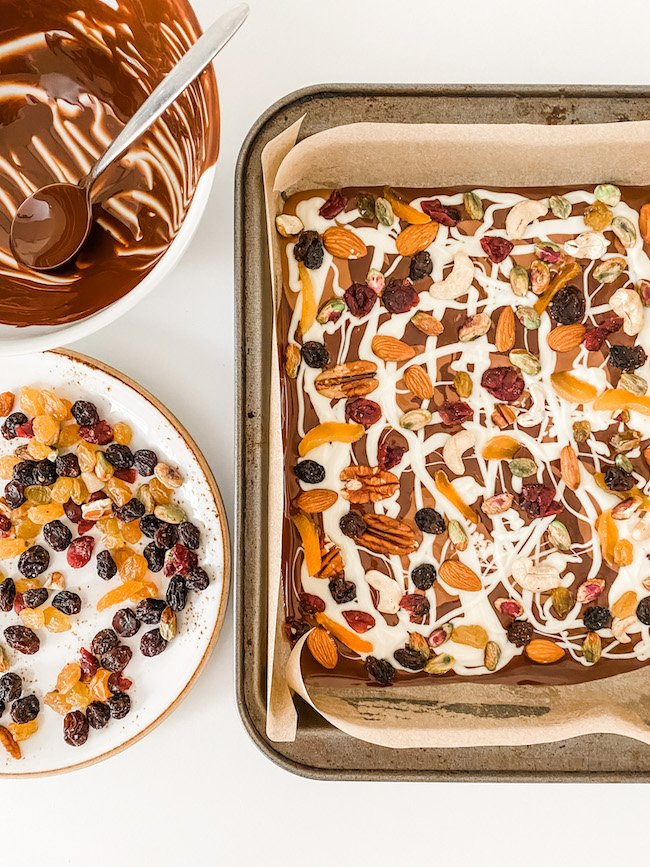 Triple Chocolate Fruit and Nut Bark topped with fruits and nuts, prepared and ready to go in the fridge