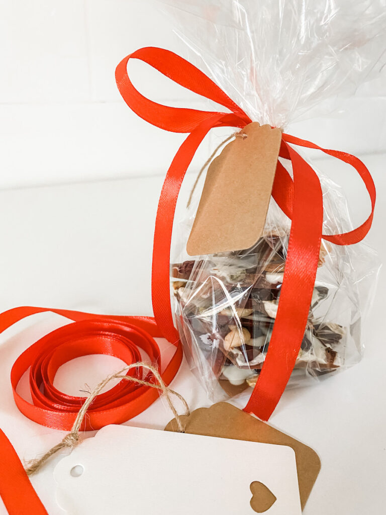 Triple Chocolate Fruit and Nut Bark wrapped in cellophane and tied with a red bow