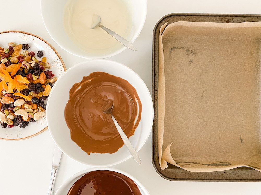 Three bowls of melted chocolate, a prepared tin and a plate of fruits and nuts