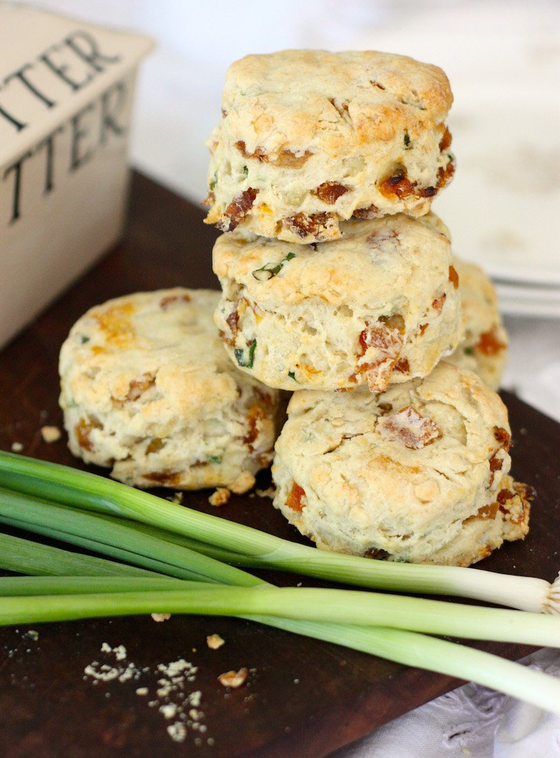 White Stilton and Apricot Scones on a board with spring onions and a butter dish