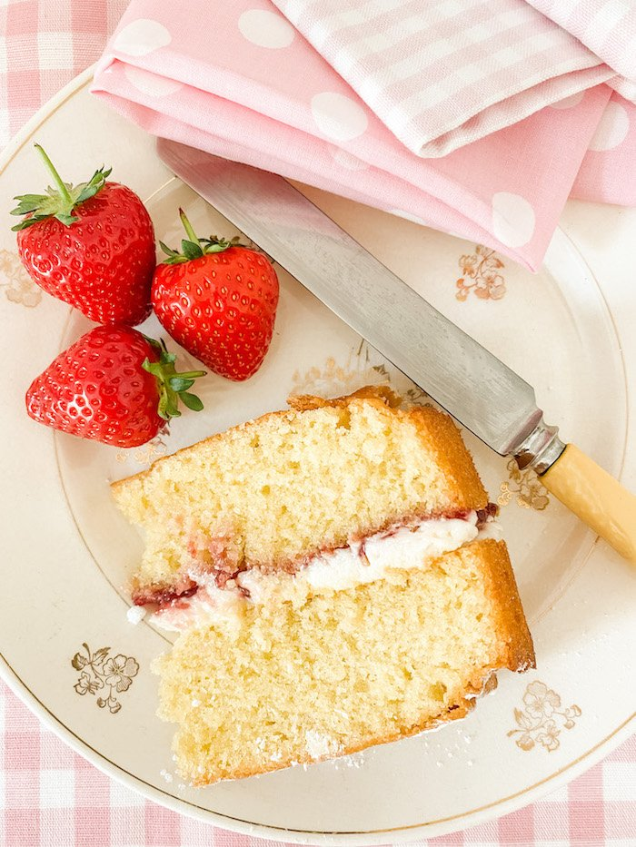 Slice of Victoria Sponge Cake and 3 strawberries on a plate with a knife and pink gingham napkins