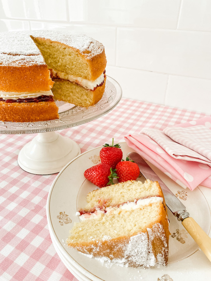 A Victoria Sponge Cake on a glass cake stand, standing on a table with a pink gingham tablecloth