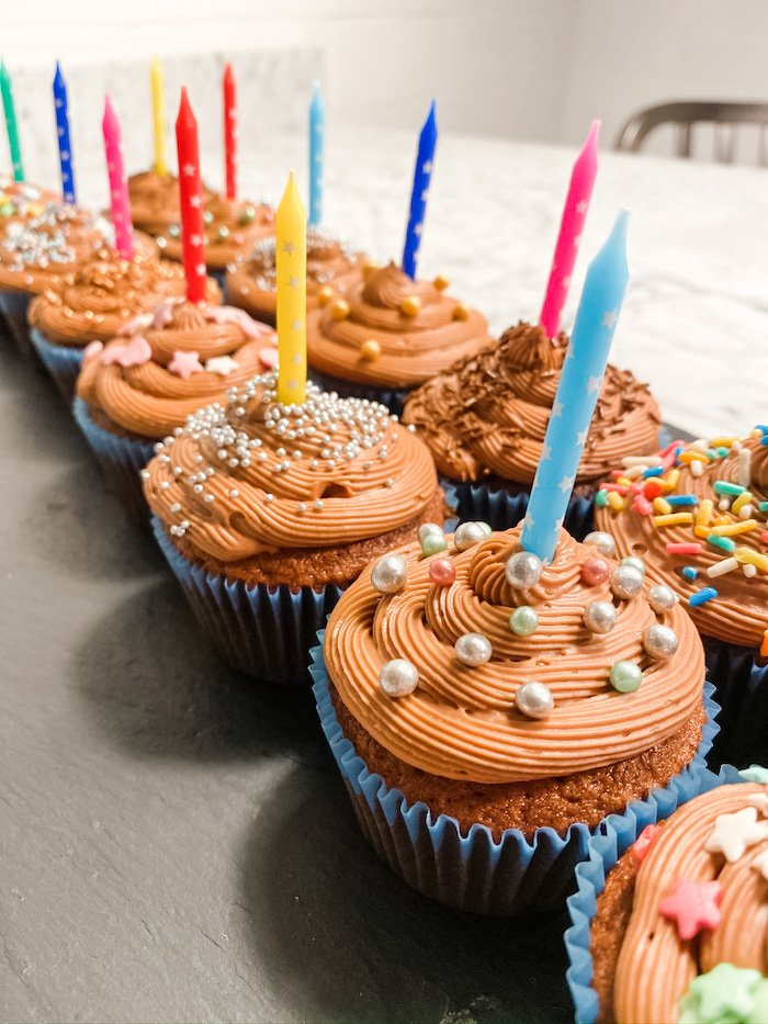 Two rows of chocolate cupcakes with candles