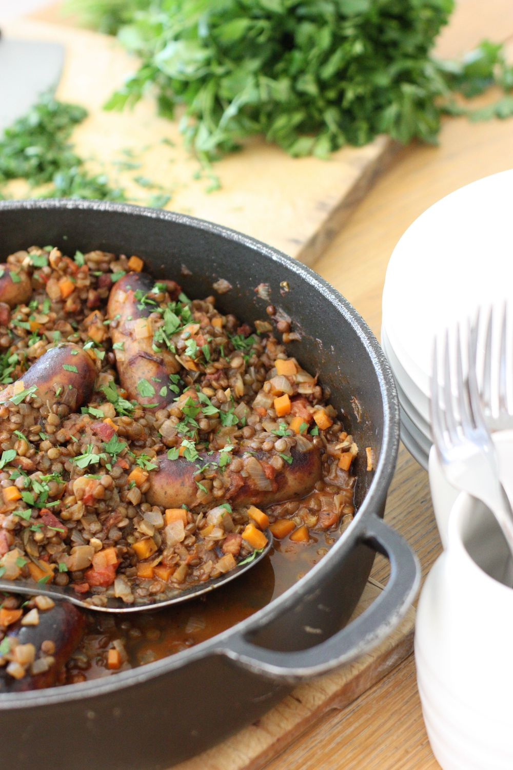 Sausage and Puy Lentil Pot in black pan with a pile of white plates