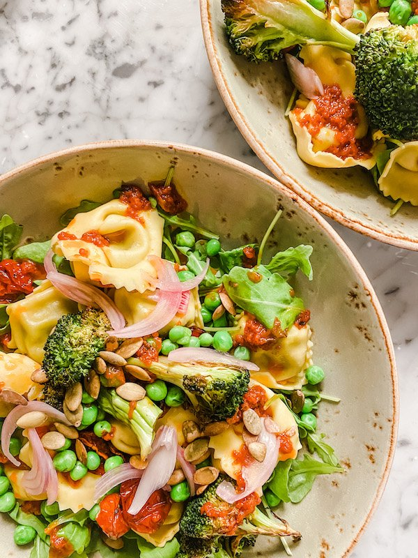 Tortellini served with spinach, peas, harissa dressing, broccoli and roasted tomatoes in a green bowl