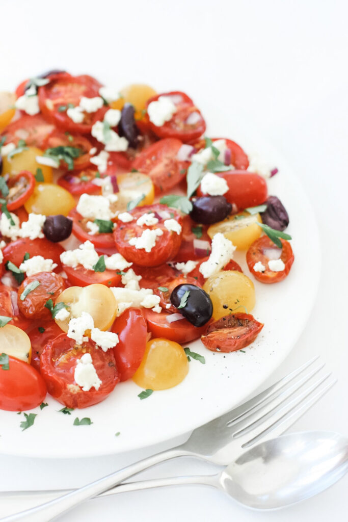 Roasted tomatoes, fresh tomatoes, feta, olives and basil on a white plate