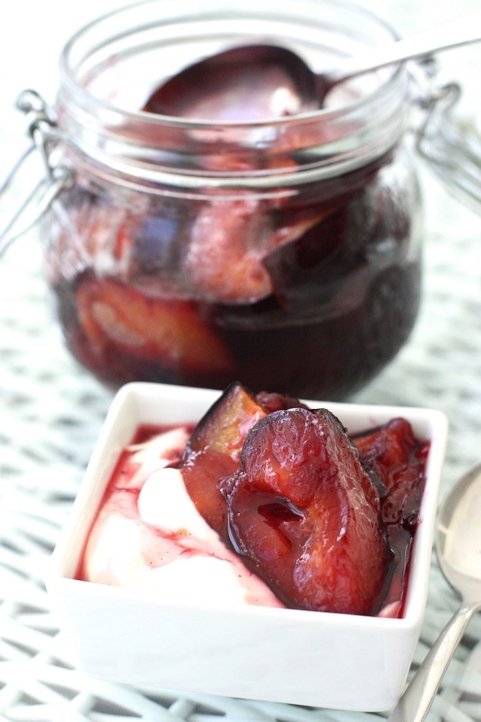 Roasted Plums with Vanilla Sugar in a small dish with yoghurt and a jar in the background