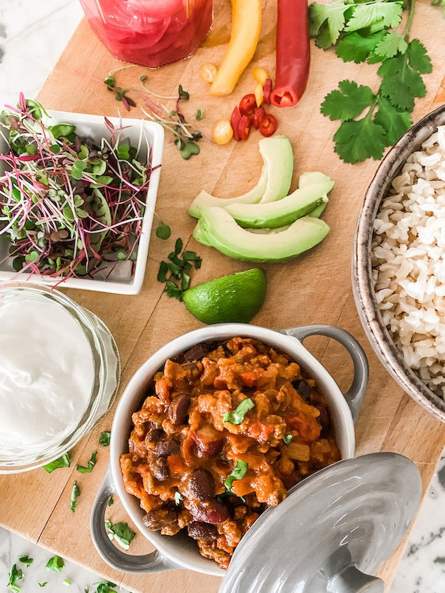Chilli con Carne in a small grey pot on a wooden board with a bowl of rice and all the toppings