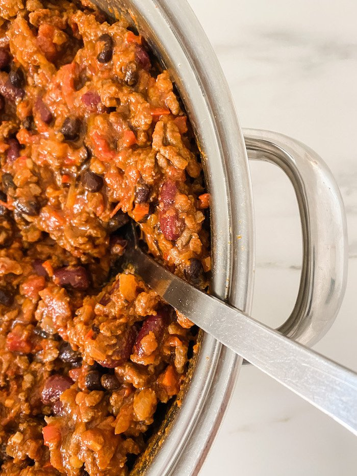 Chilli con Carne in a metal pan with a large serving spoon