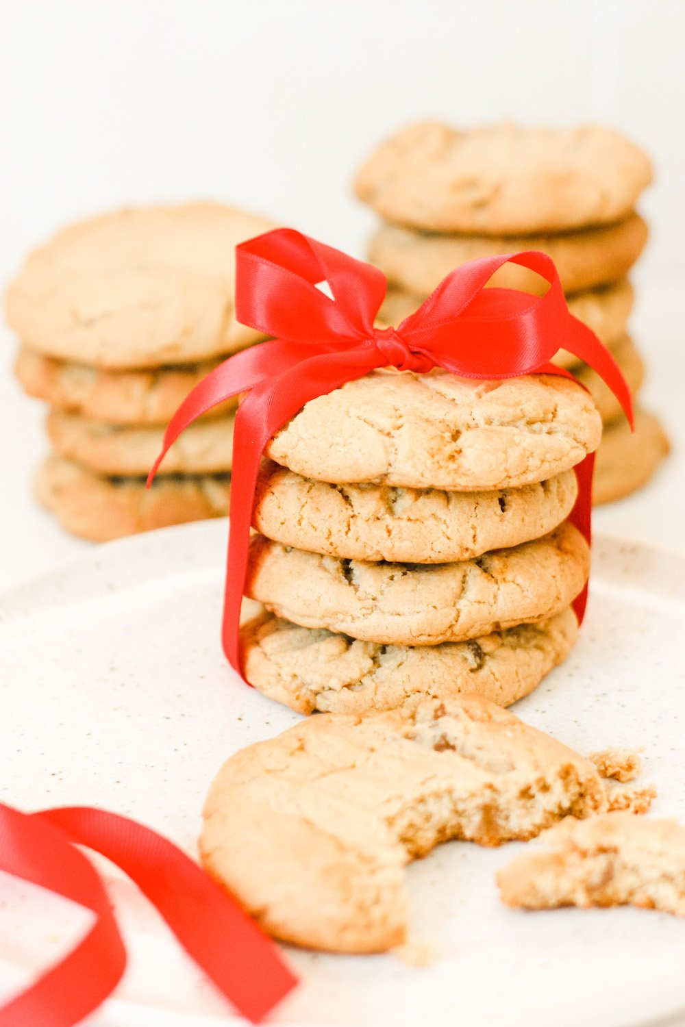 A pile of stem ginger cookies tied up with a red bow