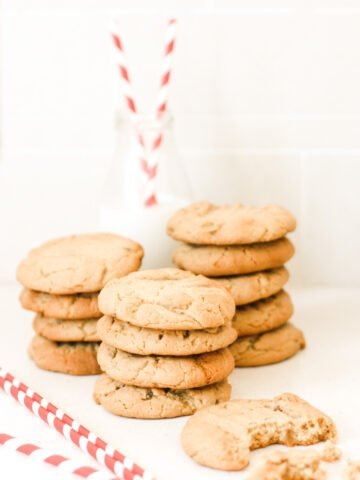 Stem ginger cookies in three piles with a bottle of milk and straws