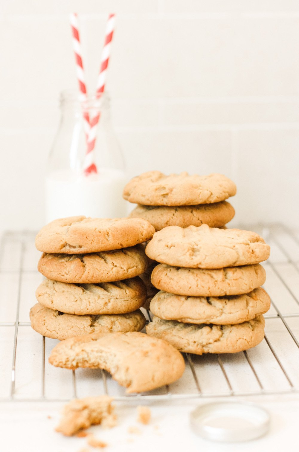 Piles of stem ginger cookies on a cooling rack with a small bottle of milk